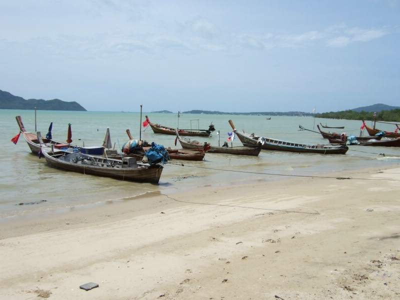 Fishing boats at the beach at noon in Phuket, Thailand